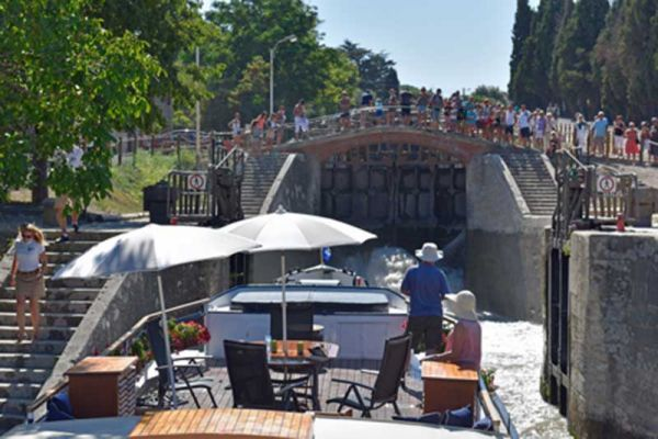 Luxury barge cruise Anjodi approaching a lock with onlookers