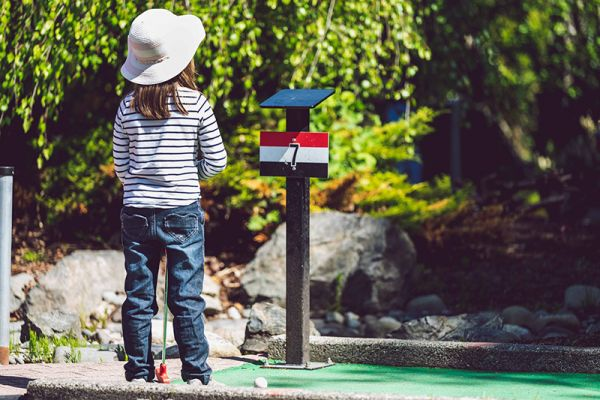 Child playing minigolf in France as part of a family charter cruise