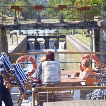 passengers wait in excitement as the luxury canal barge approaches a canal lock, france