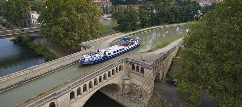 Luxury Hotel Barge Anjodi, cruising in Southern France on a viduct on the Canal du Midi