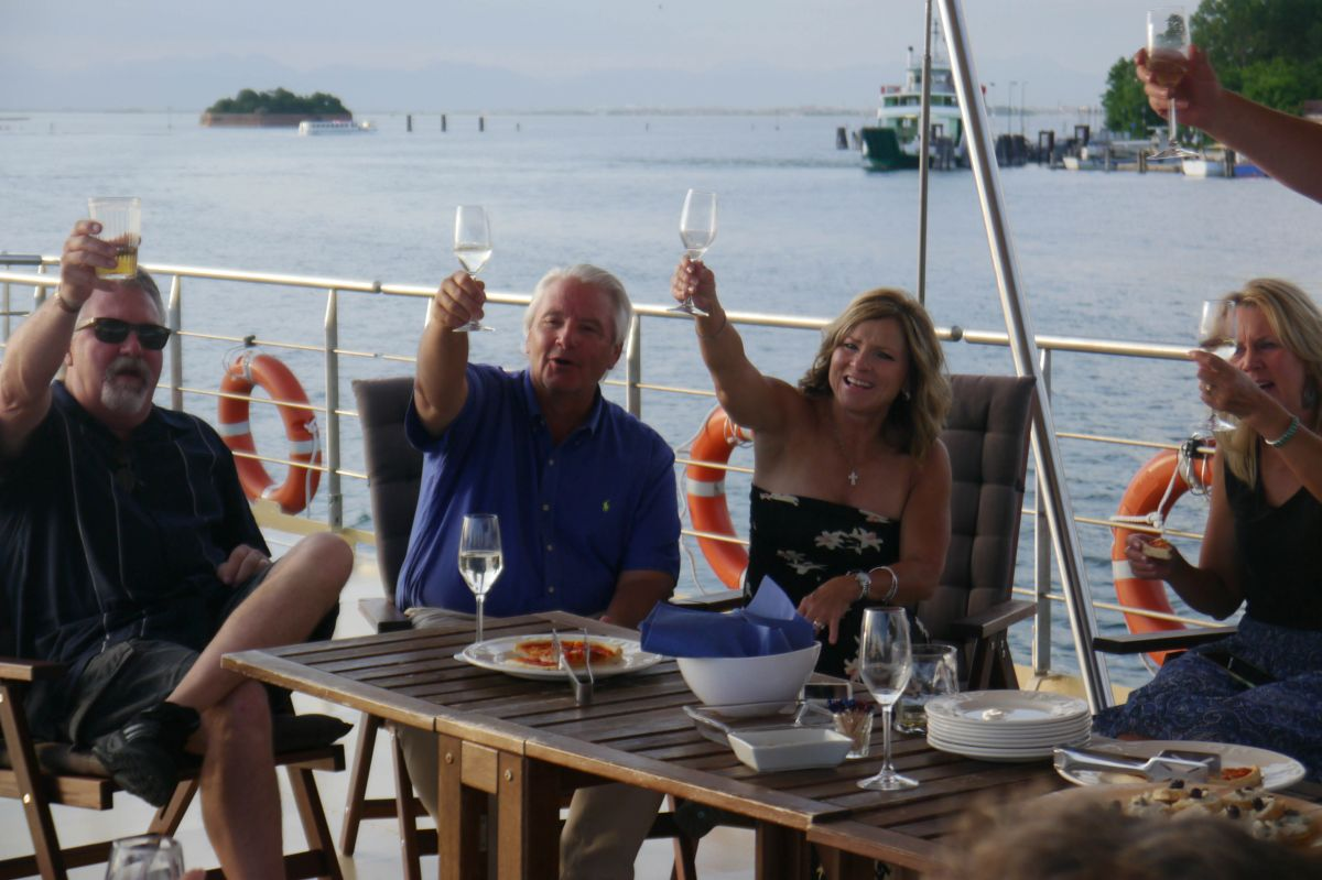 New friends toasting the day aboard luxury cruise La Bella Vita in Italy