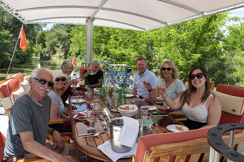 Friends or family enjoying a delicious meal aboard luxury hotel barge Athos