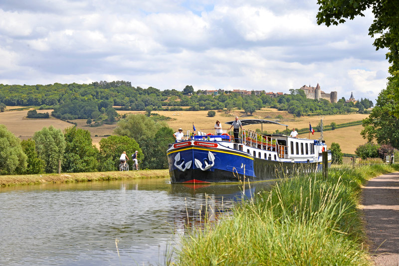 Luxury hotel barge, L'Impressionniste cruising past chateuneuf in Burgundy, France