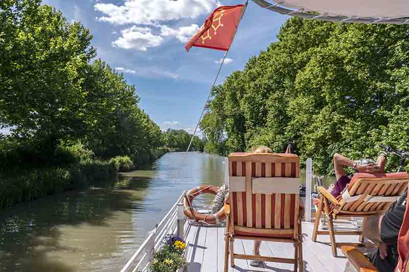 Clients relaxing on deck aboard luxury hotel barge, Athos